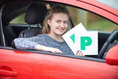 Teenage Girl Recently Passed Driving Test Holding P Plates - stock photo