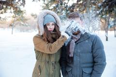 Amusing woman thowing snowball in her boyfriend face Stock Photos