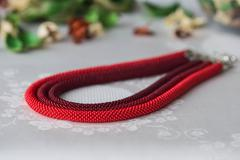 Beaded necklace of red color from three ropes Stock Photos