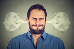 Ngry young man, blowing steam coming out of ears Stock Photos