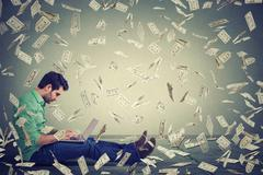 Young man using laptop sitting on floor building online business making money Stock Photos