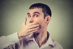 Stock Photo of Headshot of a scared adult man with hand covering his mouth