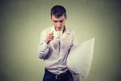 Very tired, almost falling asleep business man holding a cup of coffee and pi Stock Photos