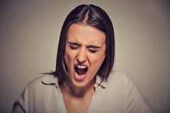 Portrait of an angry woman shouting isolated on gray wall background - stock photo
