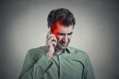 Man on the phone with headache. Cellular mobile radiation concept Stock Photos