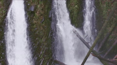 Hiker climbing near the edge of the cliff by waterfalls. - stock footage