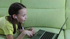 Frightened little girl looks terrible video on laptop - stock footage