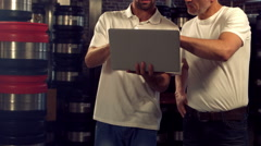 Brewery workers checking info on a laptop Stock Footage