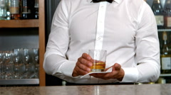 Smiling barman serving a whisky Stock Footage