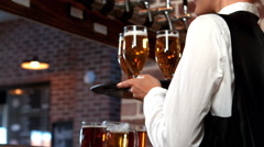 Smiling barmaid serving glasses of beer Stock Footage