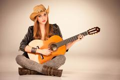 The beautiful girl in a cowboy's hat and acoustic guitar Stock Photos