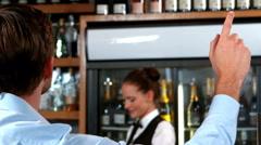 Customer raising hand to call barmaid Stock Footage