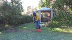 Gardener in warm clothes rake leaves on frosted garden grass in autumn. 4K Stock Footage
