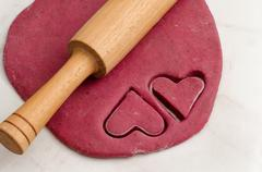 Sheet red dough with a rolling pin and cut out two heart shape cookies, prepa - stock photo