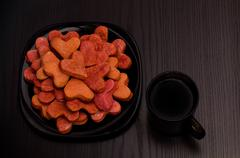 Black plate with red heart-shaped cookies and a mug of tea on a black table, - stock photo
