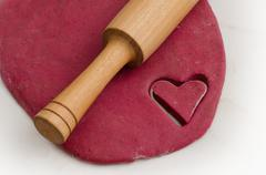 Sheet dough with red heart-shaped cut-out, preparing for Valentine's Day - stock photo