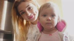 Little one years old girl and her young mother - stock footage