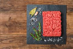 Minced meat  with seasonings and fresh rosemary - stock photo