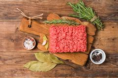 Minced meat  with seasoning and fresh rosemary - stock photo