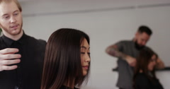 Attractive young woman having her hair styled by a hairdresser. Shot on RED Epic Stock Footage
