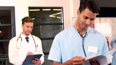 Doctors writings things on clipboards Stock Footage