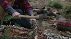 Bearded woodsman chops wood at campground in the forest, throws wood in pile. Stock Footage