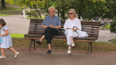 Little girl walking by senior couple in green city park, two generations meet Stock Footage