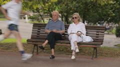 Senior man and woman having rest in city garden, social policy, pension reform Stock Footage