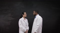 4K Portrait of man & woman in white coats, standing in front of blank blackboard Stock Footage