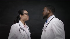 4K Portrait of doctors in white coats, standing in front of blank blackboard  Stock Footage