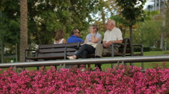 Couple of senior people sitting on bench in city garden, state social policy Stock Footage