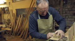 Man sandpaper grinds wood Stock Footage