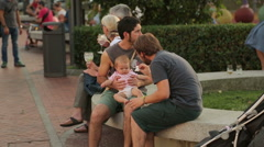 Two young men taking care of child, feeding baby girl in the park, babysitting Stock Footage