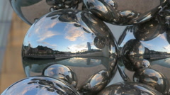 Bilbao city landscape visible in reflective spheres outside Guggenheim Museum Stock Footage