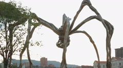 Crowd walking under Spider Maman sculpture displayed outside Guggenheim Museum Stock Footage