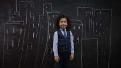 4K Little boy standing in front of blackboard with drawings of buildings - stock footage