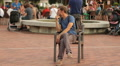 Smiling young man sitting on chair in park, making funny poses, performance Footage