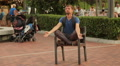 Funny man meditating in lotus position on chair at park, entertaining public Footage