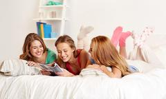 Stock Photo of friends or teen girls reading magazine at home