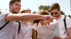 Smiling hipster friends pointing direction while holding map Stock Footage