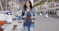 Trendy jaunty young woman enjoying a stroll Stock Footage