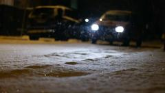 Out of focus car lights at snowing street in night. Slow motion Stock Footage