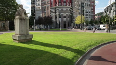 Beautiful city square with green lawns, modern buildings and historical monument Stock Footage