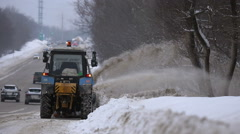 Tractors of road service clean up the snow from the roadside Stock Footage