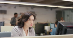 Businesswoman executive working at computer using smart phone connected to Stock Footage