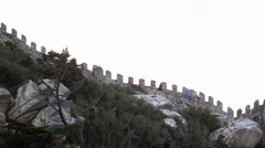 Tourists walk up Castle of the Moors fortress wall, Sintra, Portugal Stock Footage