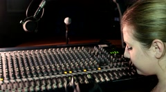 Radio Presenter DJ girl speaks into the microphone on the air big sound mixer - stock footage