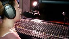 Radio presenter in headphones broadcasts live in the studio speaks mic Stock Footage
