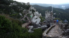 People walk down Castle of the Moors walls, Sintra, Portugal Stock Footage