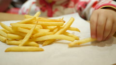 Little kid girl closeup eating french fries in a fast food restaurant Stock Footage